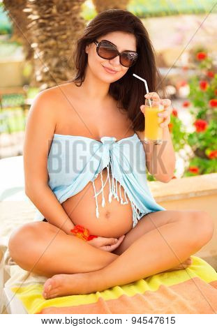 Happy pregnant woman sitting on tropical beach and drinking fresh tasty juice, spending pregnancy on exotic resort, healthy family life