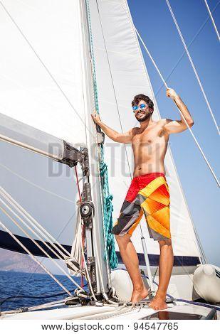 Happy man having fun on sailboat, enjoying active summer adventure, luxury beach holidays, sportive lifestyle