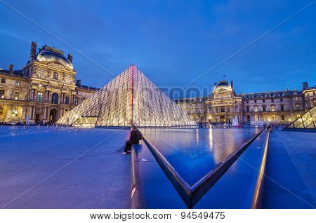 Paris, France - May 14, 2015: Tourist visit Louvre museum at twilight