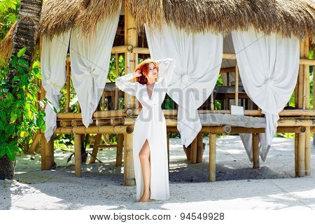 Young Beautiful Girl In White Dress Stands Next A Bamboo Hut On A Tropical Island.