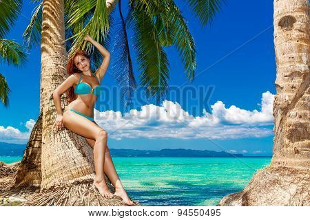 Young Beautiful Woman Under The Palm Trees On A Tropical Island. Blue Sea In The Background.