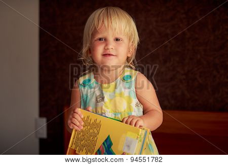 Blonde Girl Plays With Large Colorful Childish Book
