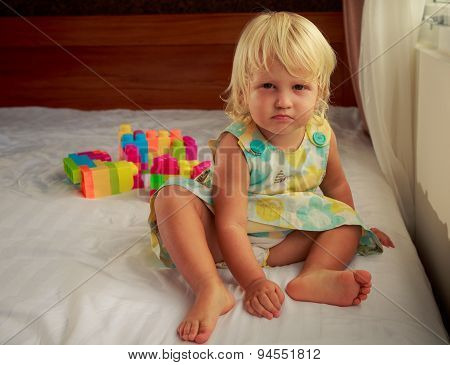 Little Blonde Girl Sits By Window On Sofa