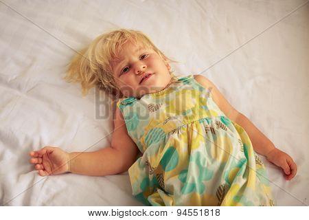 Little Blonde Girl Lies On White Blanket Of Sofa