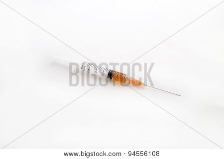 Dispensing Syringe Laying On A White Background.