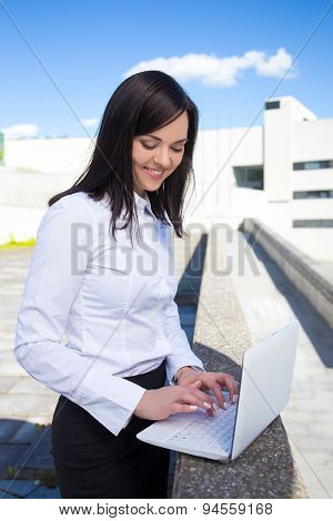 Portrait Of Beautiful Business Woman With Laptop On The Street