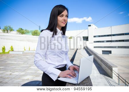 Beautiful Business Woman Working On Laptop Outside Office