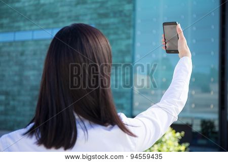 Back View Of Business Woman Making Selfie Photo On Smartphone