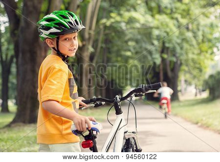 Boy In Safe Helmet With Bicycle In City Park