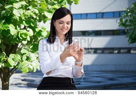 Young Business Woman Listening Music With Smartphone In City Park