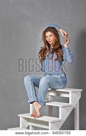 Girl In Jeans And Shirt Sitting On The Steps