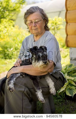 Senior Woman Hugs Her Black And Silver Miniature Schnauzer Dog In Countryside