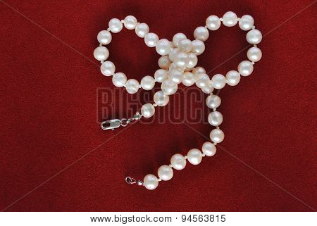 pearl necklace on red velvet background