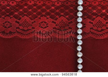 pearl string with red lace on red velvet background