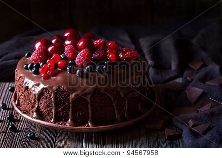 Traditional homemade chocolate cake sweet pastry dessert with brown icing, cherries, raspberry, curr
