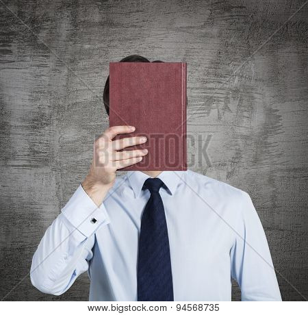 A Person Holds A Red Book In Front Of The Head. Concrete Background.