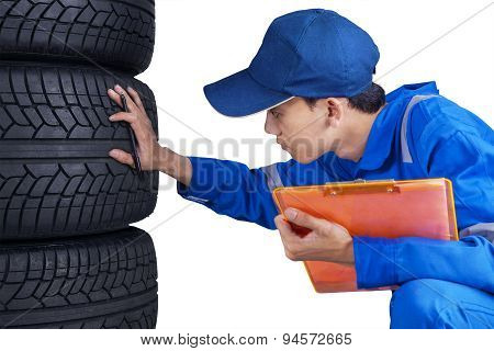 Technician With Blue Uniform Checks Tires