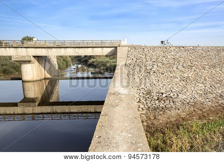 bridge weir Gameiro reflected on water and a bike - Mora, Portugal