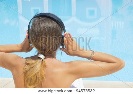 Girl Listening To Music By The Pool