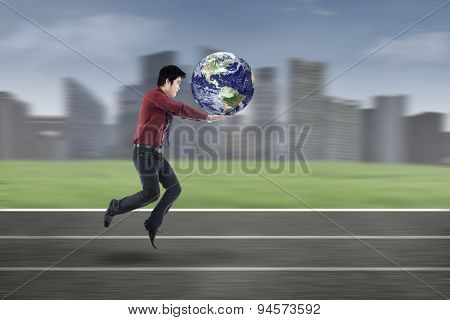 Young Businessman Running With Globe