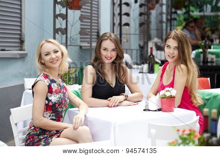 Three beautiful girlfriends woman sitting at a table in the summer city cafe