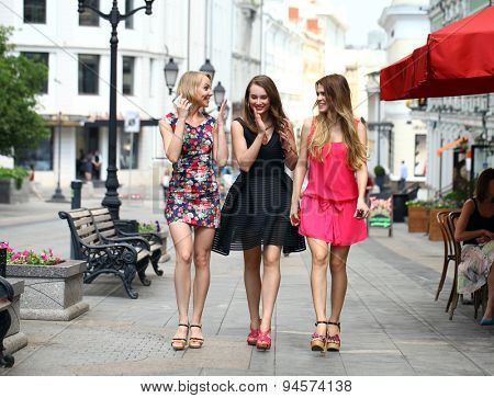 Three beautiful young women girlfriends walk on a summer street in the city center