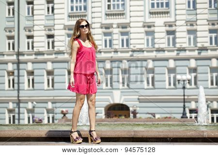 Young beautiful blonde woman in red short dress posing outdoors in sunny weather