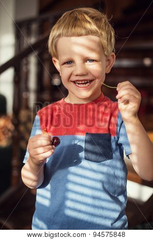 Little blond boy eating sweet cherries. Outdoor portrait