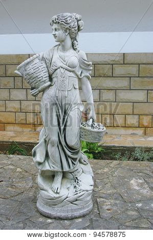 A statue of a lady in a garden