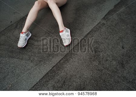 slim lady legs against ruberoid or asphalt