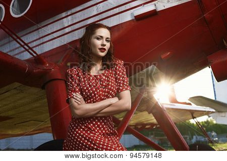 pin-up female sitting on airplane wheel in  dress