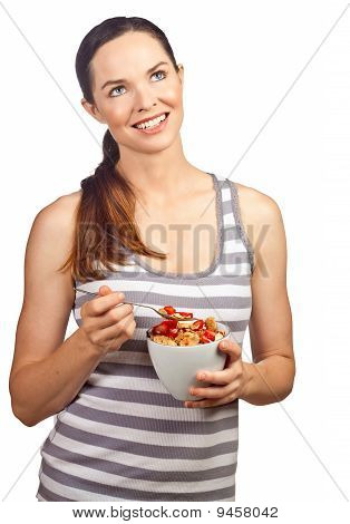 Portrait Of A Beautiful Young Woman Eating A Healthy Bowl Of Cereal With Strawberries.