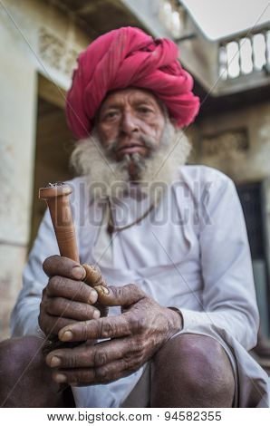 GODWAR REGION, INDIA - 12 FEBRUARY 2015: Elderly Rabari tribesman with traditional turban, clothes and long beard holds chillum. Hands in focus. Rabari or Rewari are an Indian community in Gujarat.