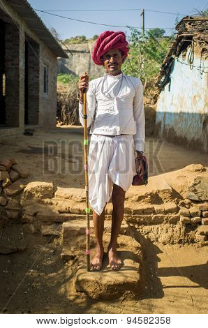 GODWAR REGION, INDIA - 13 FEBRUARY 2015: Rabari tribesman stands in courtyard with traditional clothes and holds herding stick. Rabari or Rewari are an Indian community in the state of Gujarat.