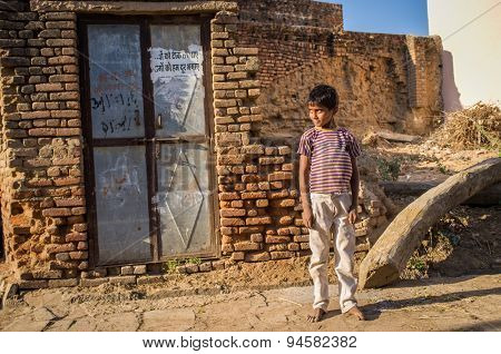 GODWAR, INDIA - 12 FEBRUARY 2015: Little barefoot boy stands in street next to ruined house.