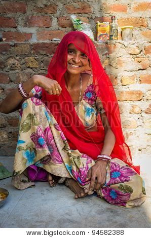 GODWAR REGION, INDIA - 13 FEBRUARY 2015: Indian woman in sari sits next to brick wall.