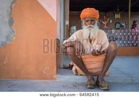 GODWAR, INDIA - 12 FEBRUARY 2015: Elderly Indian tribesman with turban in lungi sits on ground in front of temple.