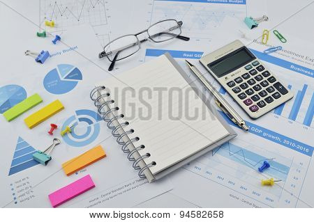 Book, Pen, Calculator, Glasses, Notes And Financial Graph