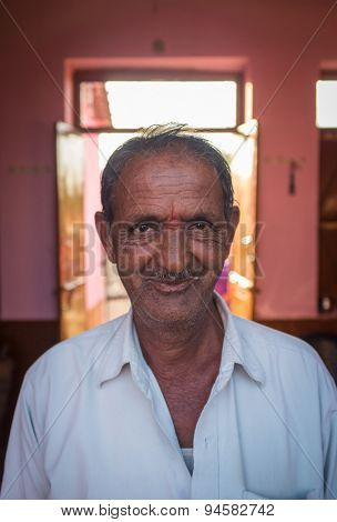 GODWAR REGION, INDIA - 12 FEBRUARY 2015: Elderly Indian man in home with door open in background.