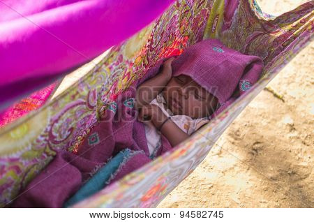 GODWAR, INDIA - 12 FEBRUARY 2015: Indian baby sleeps in makeshift crib made from blanket.