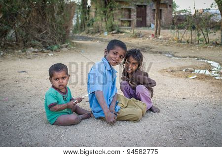GODWAR, INDIA - 12 FEBRUARY 2015: Three kids sit and play on gravel ground in village street.