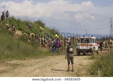 People Climbing A Muddy Rise