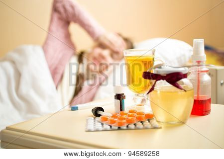 Jar With Honey And Medicines Lying On Table Next To Sick Girl Bed