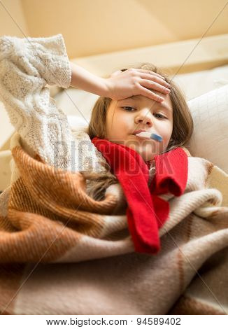 Little Girl In Scarf Lying In Bed And Measuring Temperature
