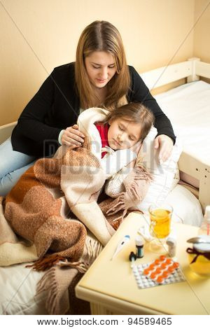 Portrait Of Caring Mother Hugging Sick Girl Lying In Bed