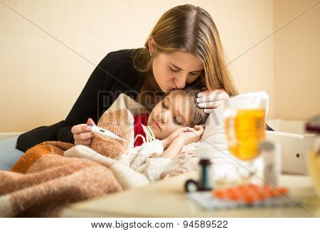 Portrait Of Caring Mother Kissing Sick Daughter In Head