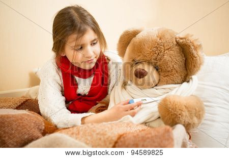 Portrait Of Girl Playing With Teddy Bear In Doctor And Patient