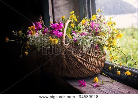 Still-life with a bunch wild flowers in a basket