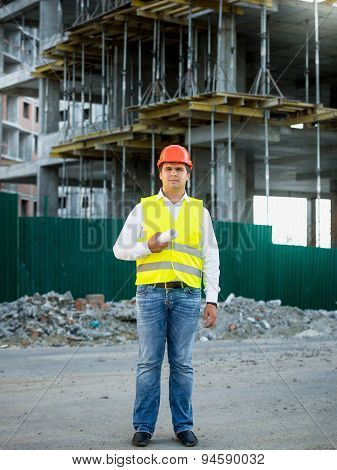 Engineer On Construction Site Posing Against Scaffolding