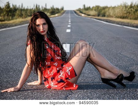 Young Woman Sitting On The Road